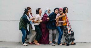 Group of seven women interpreters laughing and smiling against a white wall