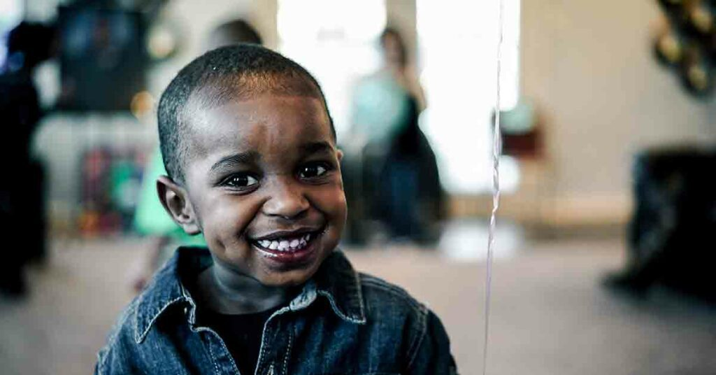 African American boy wearing a denim collared shirt and smiling