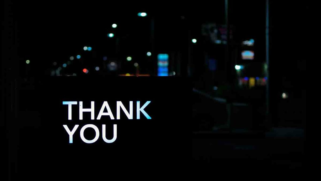 White thank you written over dark cityscape