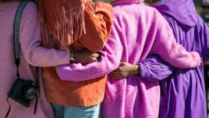Four women who all live in the same community embrace