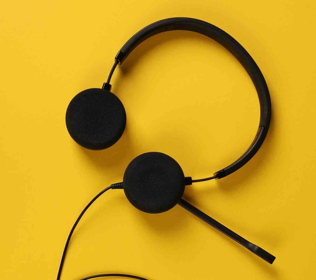 A headset that a video remote interpreter would use lying against a yellow background.