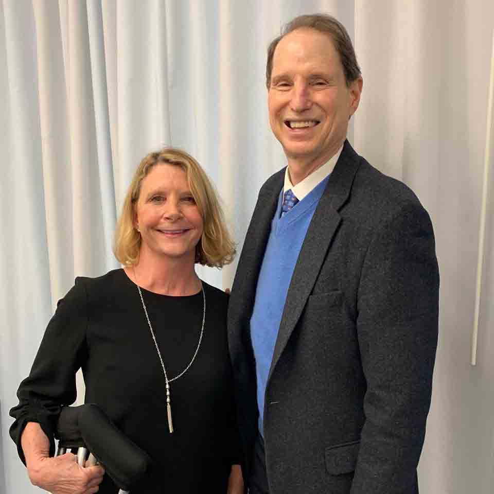 Kristin Quinlan stands next to Oregon Senator Ron Wyden. The two are posing for a picture and smiling.