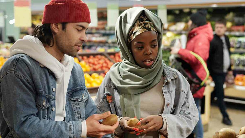 Man and woman both holding kiwis in mid-discussion at a grocery store. The man is wearing a red hat, sweatshirt, and denim jacket. The woman is wearing a mint headscarf and denim jacket.