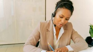 Female telephone interpreter sitting at a desk. She's looking down and taking notes while interpreting over the phone.