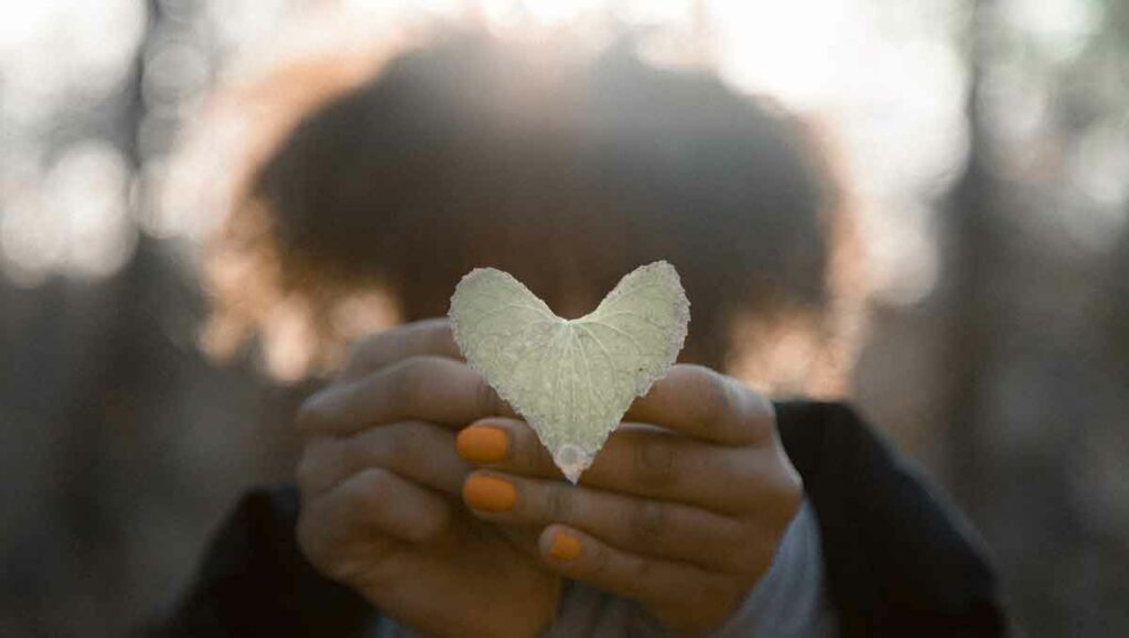 Woman holding a leaf shaped like a heart.