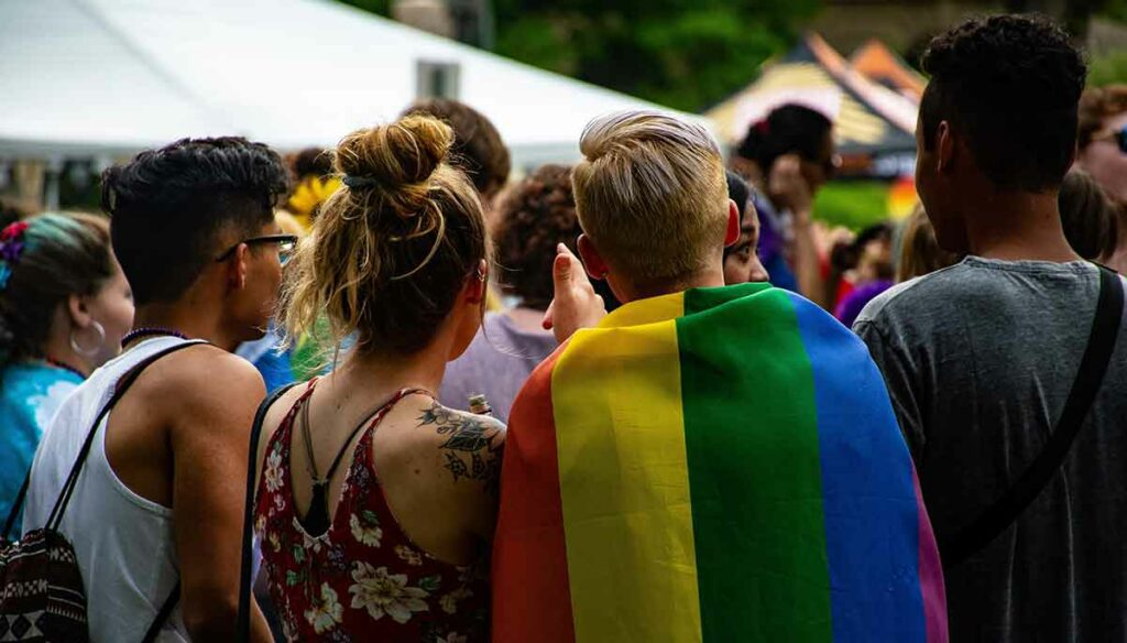 A group of friends in a crowd look at the festivities around them. A young male wears the Pride flag around his shoulders.