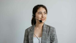 Female interpreter wearing headset looking to her left and smiling.