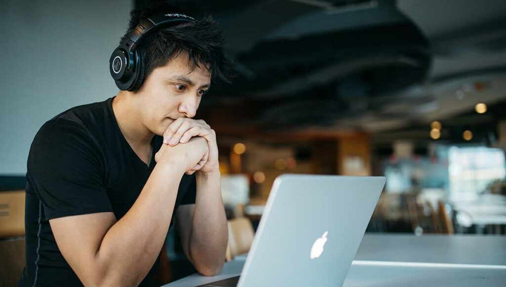 Male wearing headphones stares at his laptop while studying for his medical interpreter certification
