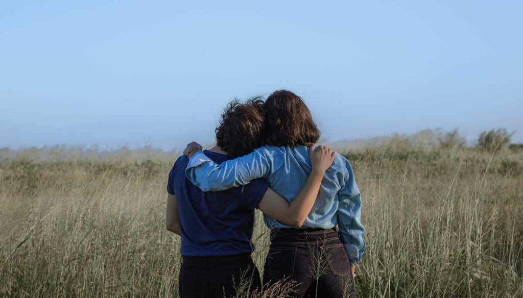 Two friends side hugging looking out over a field. One friend has their head on the other's shoulder.