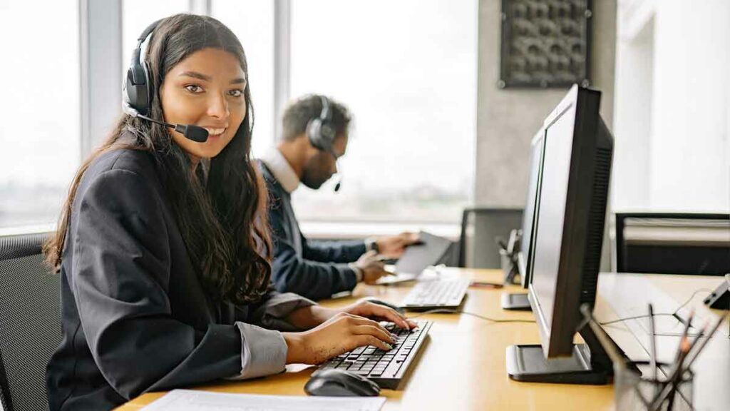 Female call center agent wearing headset and sitting next to her male colleague at her workstation. She is happy because she just used telephone interpretation services.