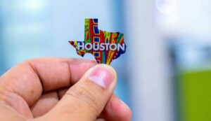 Close-up of a hand holding a pin in the shape of Texas. The pin is colorful and has Houston written on it.