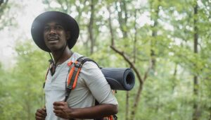 Young Black man wearing a hat and holding the straps on his backpack. He's on an overnight hiking trip in the woods.