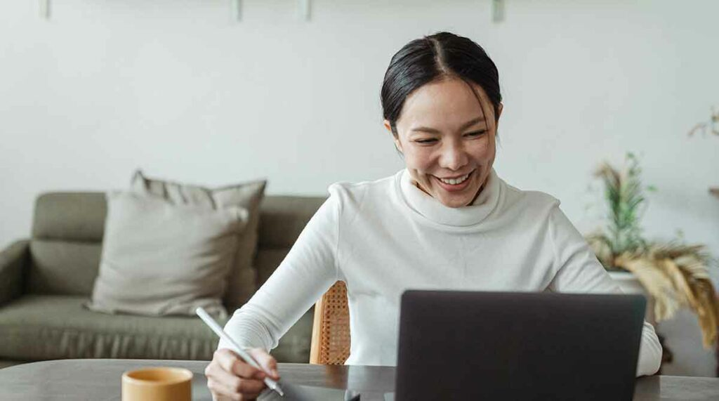 A female video remote interpreter smiles while sitting at her laptop. She's ready to take notes.
