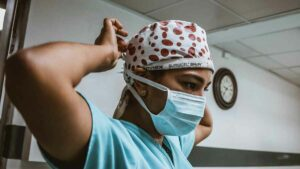 Female on-site healthcare interpreter ties a medical mask on her face. She's wearing scrubs and a white surgical cap with red dots.